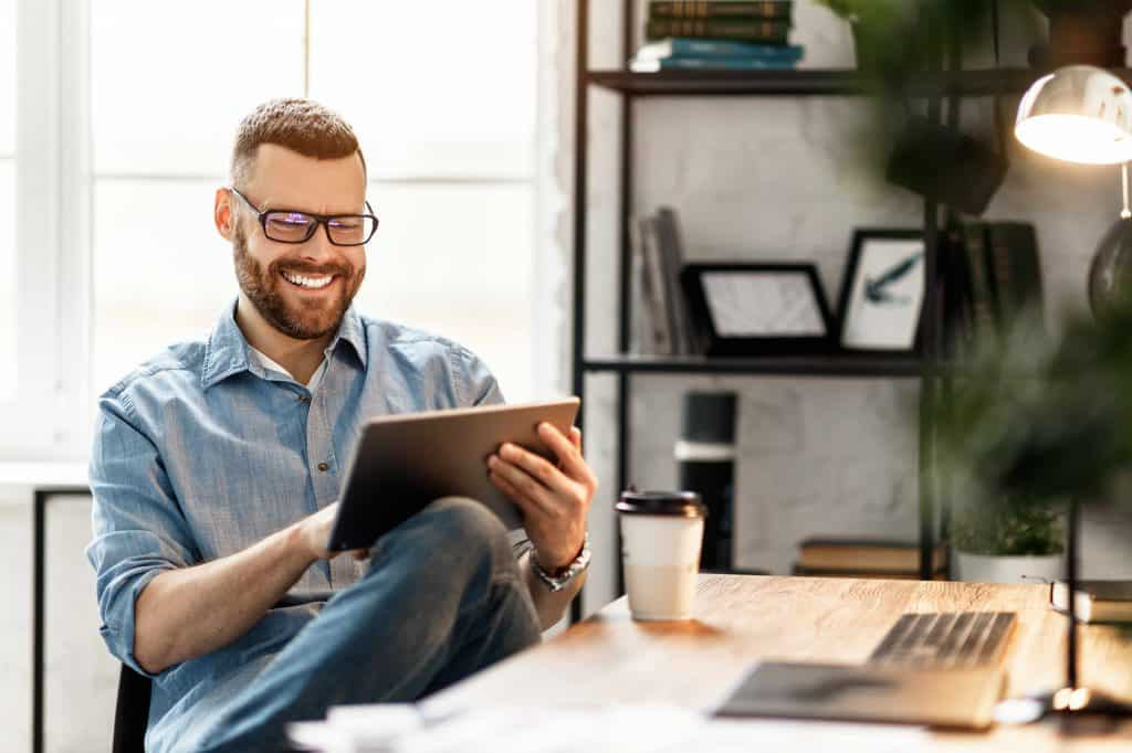 Side view of cheerful young male in casual wear and glasses using tablet while sitting with takeaway coffee at workplace with large monitor